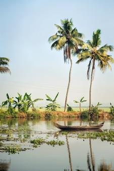 ヤシの木のある美しいアレッピーの背水の風景に乗った小さな地元の漁船