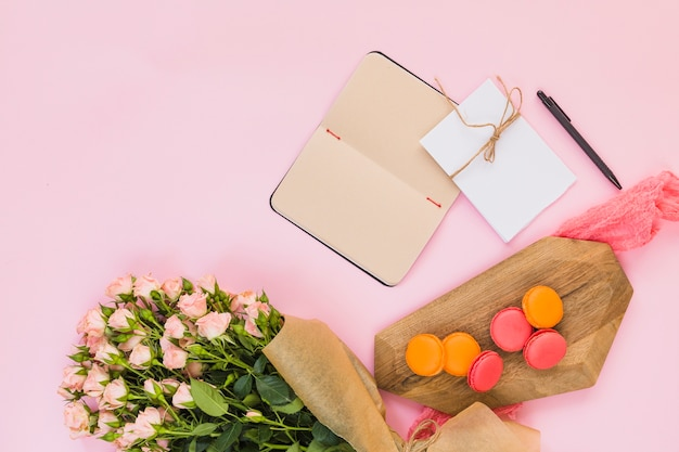 Small macaroons on chopping board; diary; card; pen and flower bouquet against pink background