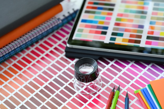 Small magnifying glass on top of color palette and swatches with different color shades working