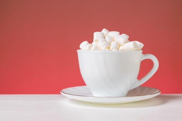 ピンクの背景の白いテーブルの上の白いカップの小さなマシュマロスライス。美味しいデザート。