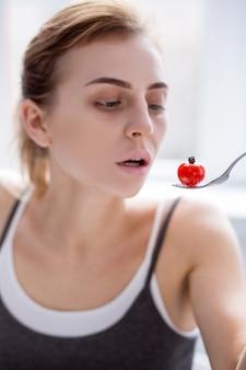 少量の食事。元気のない若い女性が食べている小さなトマトの選択的な焦点