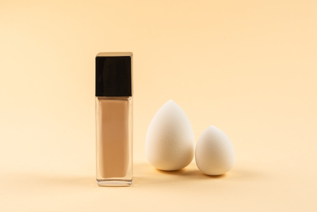 Small, medium and large  white beauty blender and makeup foundation on beige