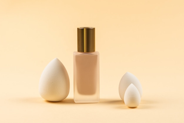 Small, medium and large  white beauty blender and makeup foundation