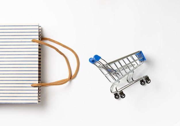 Маленькая металлическая тележка с хозяйственной сумкой на белом фоне
