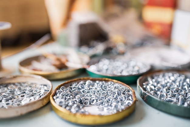 작은 금속 너트 볼트와 렌치가 어셈블러의 작업 테이블에 혼란스러운 순서로 놓여 있습니다. 패스너 및 건설 주제에 대한 배경 개념입니다. 수리 및 예비 부품 개념