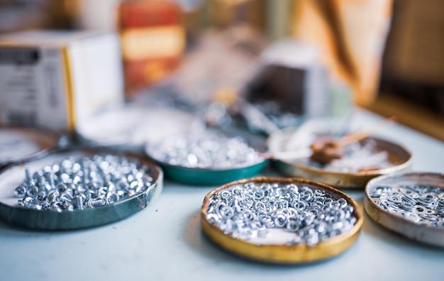 작은 금속 너트 볼트와 렌치가 어셈블러의 작업 테이블에 놓여 있습니다.