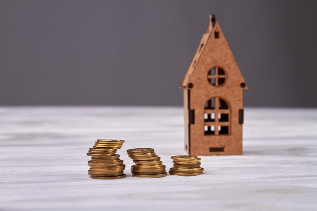 コインの山が付いている小さなミニチュアの家。