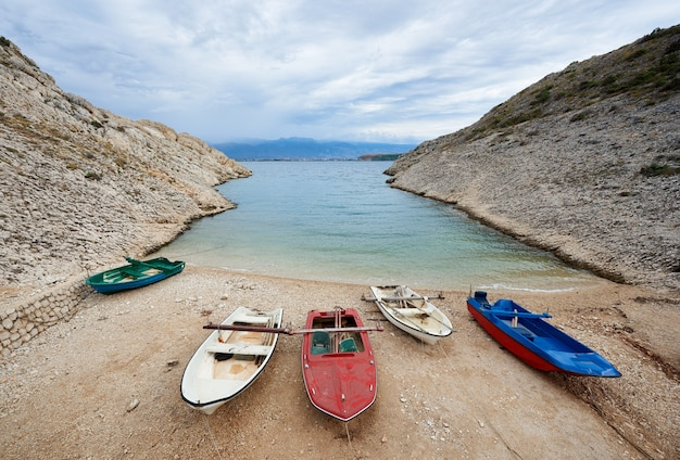 Small motor rental boats on cozy harbor coast among high rocky shores tied to pier with ropes on clear lagoon water and bright cloudy sky background. tourism, fishing, diving, recreation concept.