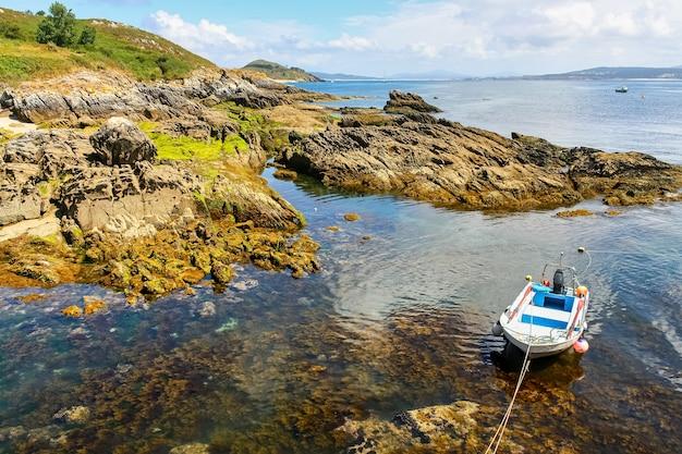 透明な海のある海の岩の隣にある小さなモーターボート。