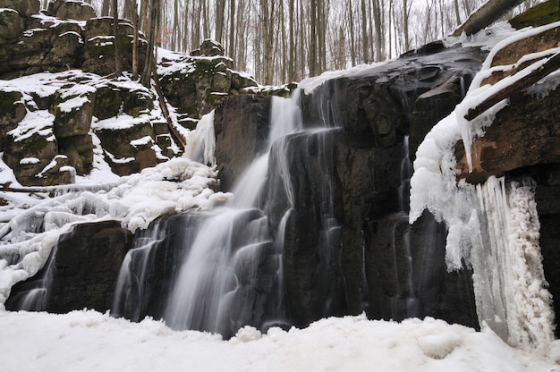 A small mountain waterfall covered in snow
