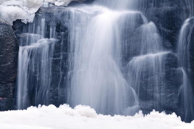 Небольшой горный водопад зимой, красивый горный ручей в заснеженном лесу, зимний пейзаж