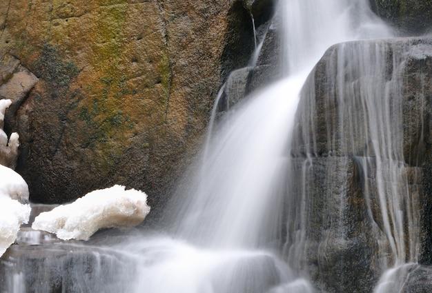 Small mountain waterfall in winter