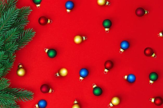 Маленькие разноцветные елочные шары, падающие из сосны ветви на красной бумаге. рождественский фон вид сверху.