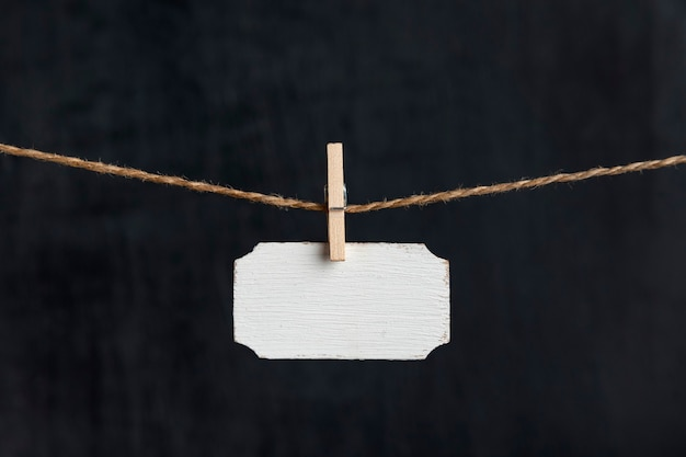 Small nameplate.blank wooden sign hang with clothespins on rope on black background. copy space.