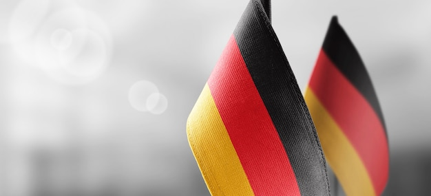 Small national flags of germany on a light blurry wall