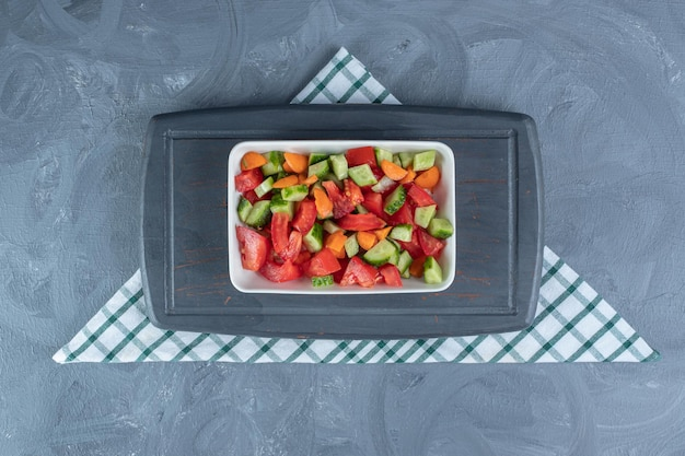 Small navy tray under a platter of shepherd's salad mixed with carrot slices on marble table.
