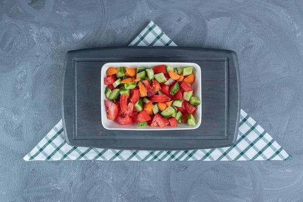 Небольшой темно-синий поднос под тарелкой пастушьего салата, смешанного с ломтиками моркови, на мраморном столе.