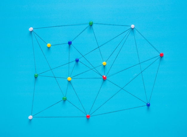 Small network of thumbtack connections arrangement of colorful pins linked together with a string