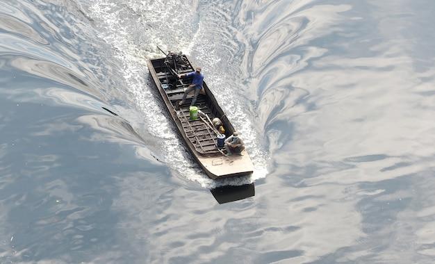 작은 오래 된 긴 꼬리 보트와 아시아 남자와 작은 강에서 항해.