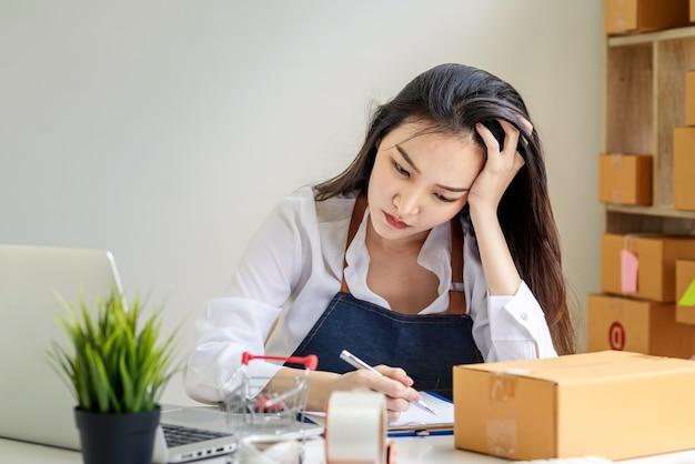 エプロンを身に着けている小さなオンラインビジネスオーナーのアジア人女性は、自宅で小包ボックスでメモを取る頭痛を強調しました。