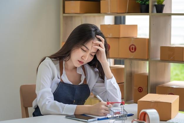 앞치마를 입은 작은 온라인 비즈니스 소유자 아시아 여성은 집에서 소포 상자로 메모를 하는 두통을 강조했습니다.
