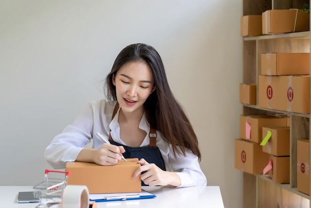 自宅の顧客のために小包ボックスに住所を書いている小さなオンラインビジネスオーナーのアジア人女性。
