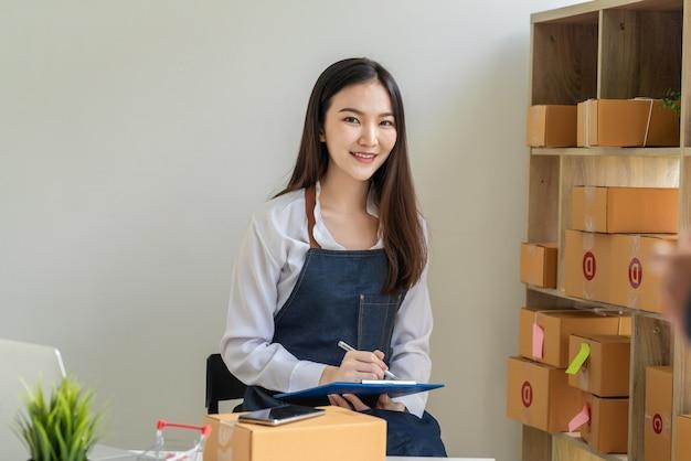 Владелец малого онлайн-бизнеса смотрит в камеру и принимает заказ, помещенный дома.