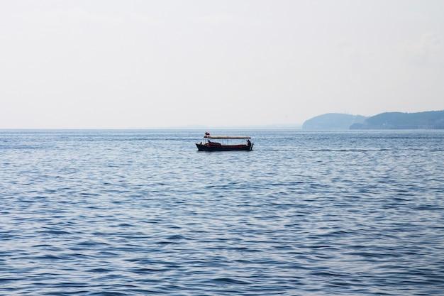 夜明けに海に屋根のある小さなオープンボート。朝の海釣り