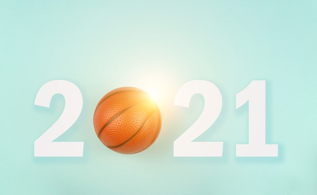 Small orange ball for basketball sport game on blue background with text 2021 and sunshine.