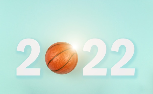 Small orange ball for basketball sport game on blue background with text 2022.