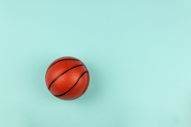 Small orange ball for basketball sport game on blue background.