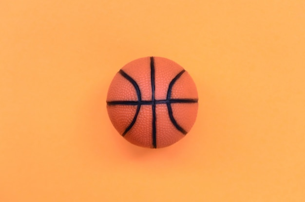 Small orange ball for basketball sport game lies on texture background of fashion pastel orange color paper in minimal concept