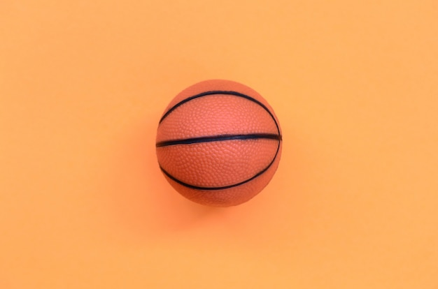 Small orange ball for basketball sport game lies on texture pastel orange