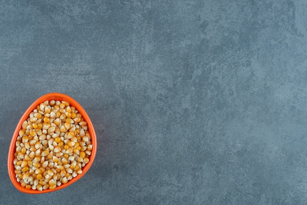Small orange bowl filled to the brim with fresh corn grains on marble background. high quality photo