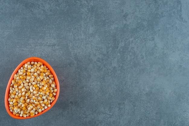 Маленькая оранжевая миска, доверху заполненная свежими кукурузными зернами на мраморном фоне. фото высокого качества