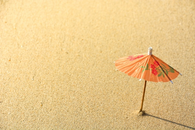 Small orange cocktail paper umbrella on the beach sand with the sunlight on the evening
