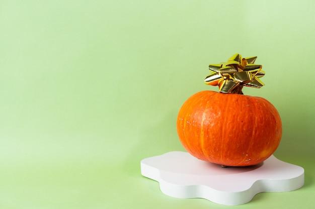 コピースペースと緑の背景に小さなオレンジ色のカボチャ。ハロウィーンや感謝祭のコンセプトのお祝い。ハロウィーンの化粧品表彰台。秋の静物。