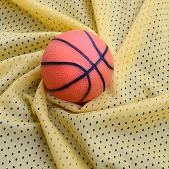 Small orange rubber basketball lies on a yellow sport jersey clothing fabric texture and background with many folds