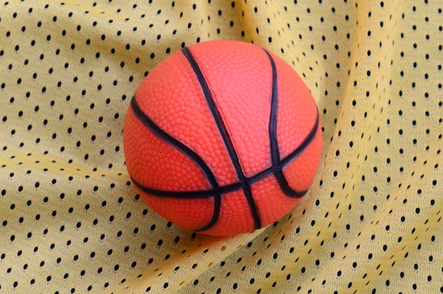 Small orange rubber basketball lies on a yellow sport jersey clothing fabric texture