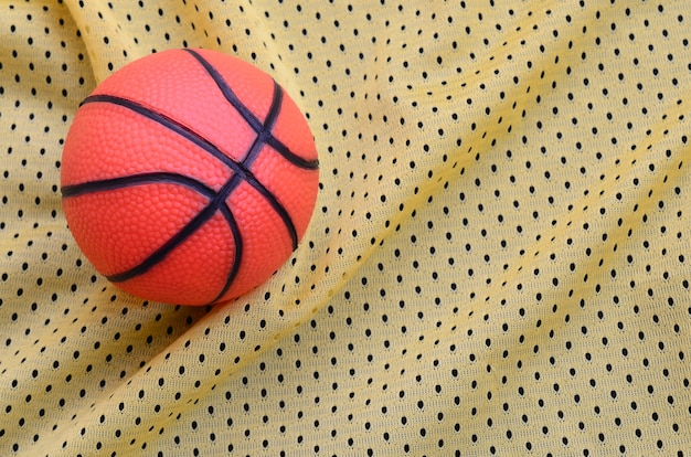 Small orange rubber basketball lies on a yellow sport jersey