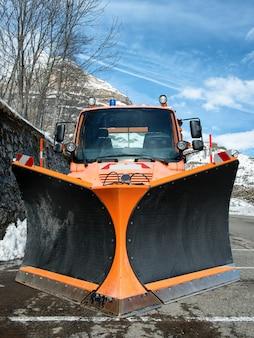 Small orange truck using snow plow