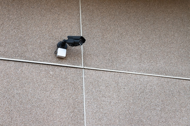 Small outdoor surveillance camera attached to the wall