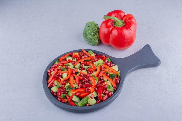 大理石の背景にピーマンとブロッコリーの横にある野菜サラダの小さな鍋。
