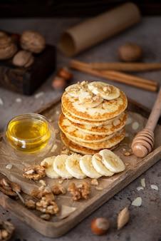 木製のトレイにバナナ、クルミ、蜂蜜の小さなパンケーキ