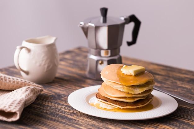 木製のテーブルにメープルシロップとバターを添えた小さなパンケーキ。朝食のコンセプト。