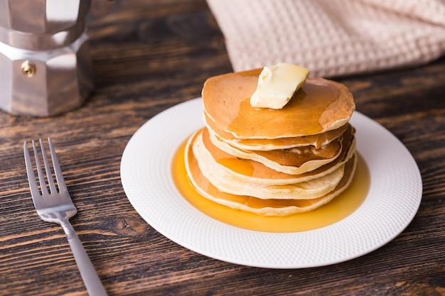木製のテーブルにメープルシロップとバターの小さなパンケーキ