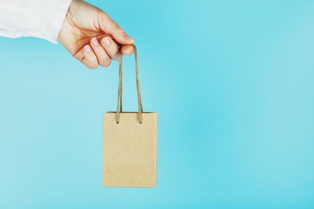 Маленький бумажный пакет на расстоянии вытянутой руки, на синем фоне. макет упаковочного шаблона с местом для копирования, рекламы.
