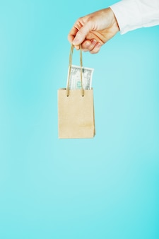 Small paper bag in hand with us dollars on a blue background. layout of the packaging template with space for copying, advertising.
