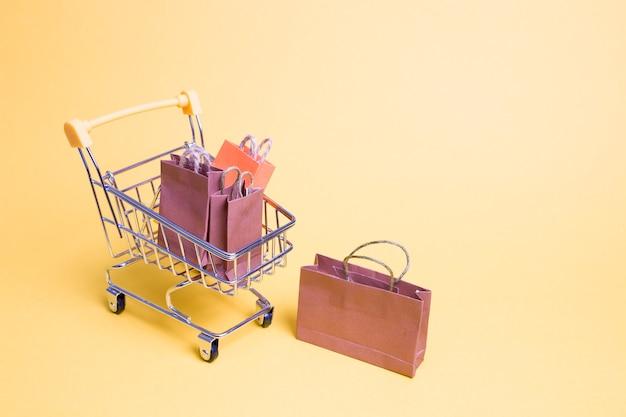 노란색 배경에 미니어처 쇼핑 트롤리에 작은 종이 봉지