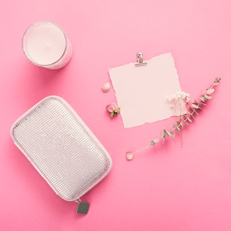 Small paper with branches, candle and clutch on table